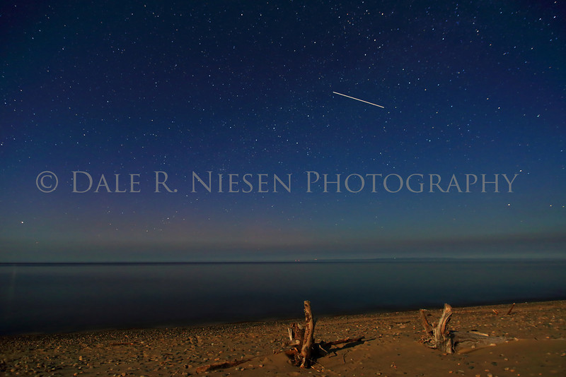 Whitefish Point on the night of June 6 - 7, 2014.  Faint aurora low at the horizon with air glow above and moon light on the beach make for soft pastel like colors in this capture over Lake Superior at Whitefish Point.   To add to the photo a satellite or the International Space Station was captured as it made a pass overhead.