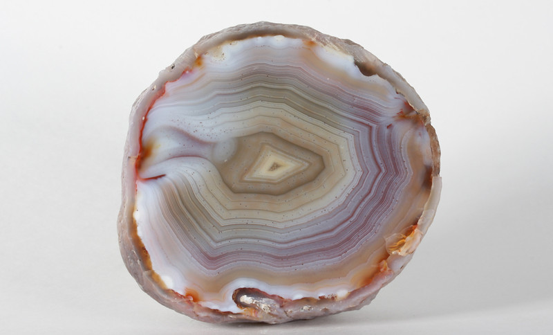 "#716 Paso Berwyn Agate, Chubut Province, Patagonia, Argentina<br /> Long exposure on the surface of the Chubut Desert has leached the color from the edges, producing a lovely aura. Exterior has been sandblasted velvety smooth, a nice agate to hold.<br /> 2 x 1 7/8 x 1"" 0.23 lb<br /> All agates in the sample galleries have been SOLD."