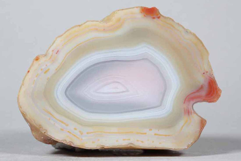 "#0219 Paso Berwyn Agate, Chubut Province, Patagonia, Argentina<br /> One could hardly ask for a more pristine agate, there are two very distincly different color zones, earthy yellows in the outer bands and cool blue gray to pink in the center. The bright red accents make it even more lively.<br /> 3 x 2 1/4 x 1 3/4"" 0.39 lb<br /> All agates in the sample galleries have been SOLD."