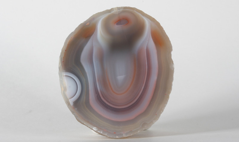 "#703 Paso Berwyn Agate, Chubut Province, Patagonia, Argentina<br /> This is one of the strangest agates I've ever seen, and it is surrealistically beautiful. The white circle on the left is a true eye and there is another on the back of the perfect exterior. This is the first true eye agate I've seen from Patagonia. There is a faint line from a healed fracture that ran down (and perhaps explains) the form at the top that seems to protrude above the surface of the agate into three dimensions. <br /> 1 7/8 x 1 5/8 x 1"" 0.15 lb<br /> All agates in the sample galleries have been SOLD."
