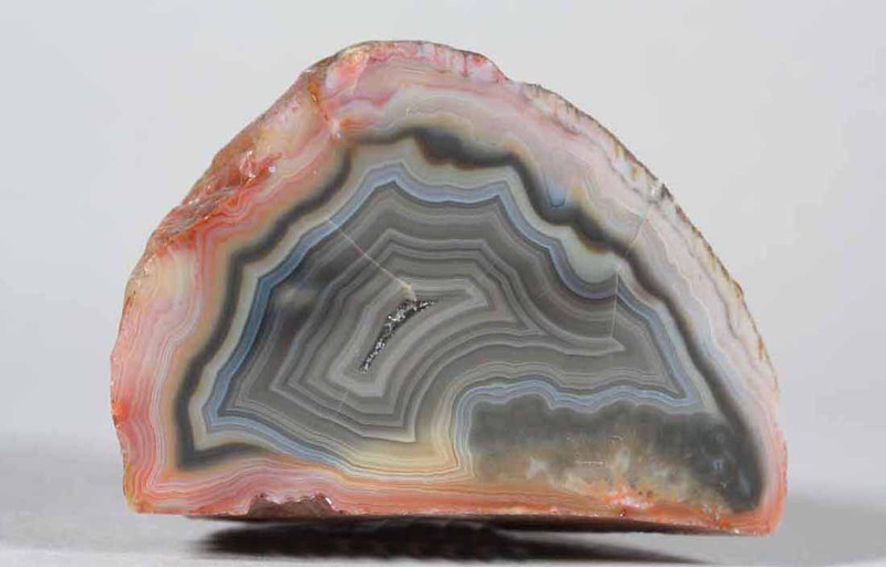 "#0206 Agate, La Manea, Patagonia, Argentina<br /> Although there are two hairline fractures, much more visible in a photograph like this than in the hand, the fortification and interesting color events make this a very beautiful specimen. <br /> 2 3/4 x 2 x 1 1/2"" 0.32 lb<br /> All agates in the sample galleries have been SOLD."