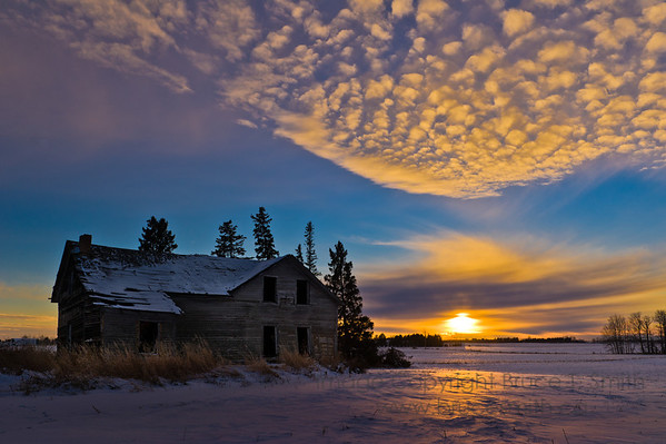 Abandoned farmhouse under a winter sunset