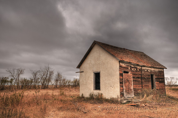 Abandoned farm building under a moody sky
