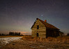 An old abandoned farmhouse under the moonlight, with a hint of aurora borealis in the sky beyond.