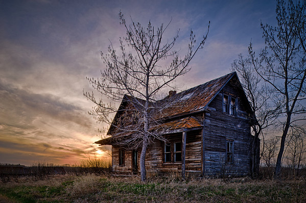 Abandoned farmhouse at sunset