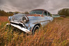 Old Pontiac rusting away in a field