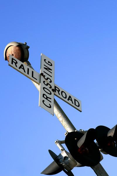 Railroad crossing against a blue sky.