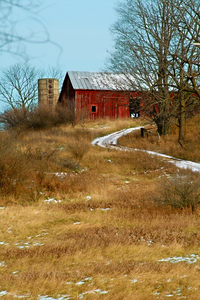 An old barn up a twisting rural drive.