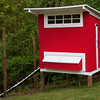 New red chicken coop in the woods.