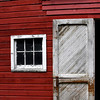 Bright red barn with a faded, peeling white door.