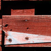 Detail of a rusted hinge of a vintage red barn.