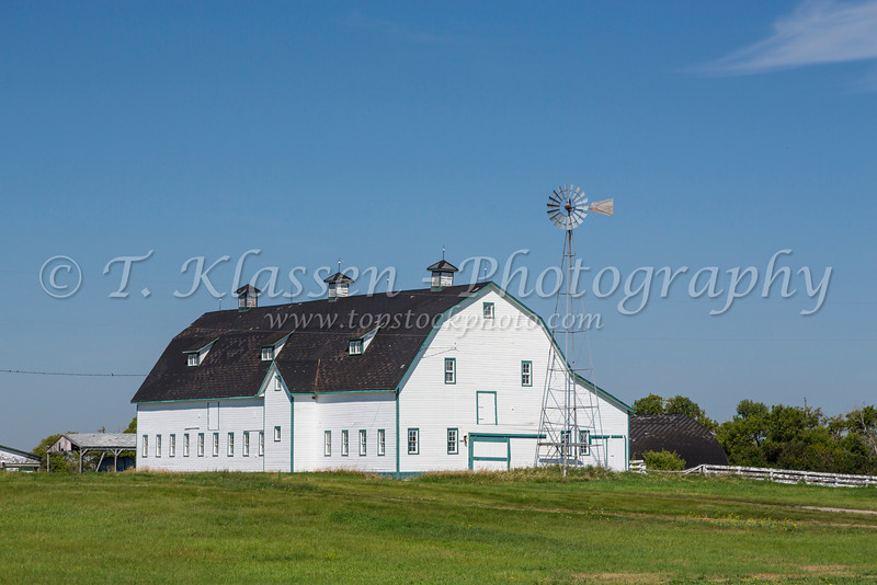 A white barn and windmill at the Hill Gresgent Farm near Elgin, Manitoba, Canada.
