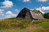 An old barn with a broken back on the prairies in southern, Manitoba, Canada.