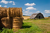 Hay bales and an old barn on the southern Manitoba prairies, Canada.