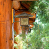 Lantern on the side of a log cabin.