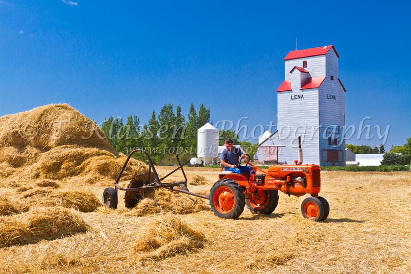 Old time baling of straw at the Charlie Baldock farm at Lena, Manitoba, Canada.