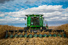 A John Deere combine harvesting corn on the Froese farm near Winkler, Manitoba, Canada.