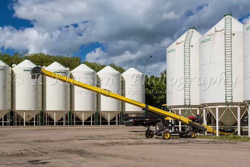 Grain bins and yellow farm equipment on the Froese Enterprises farm near Winkler, Manitoba, Canada.