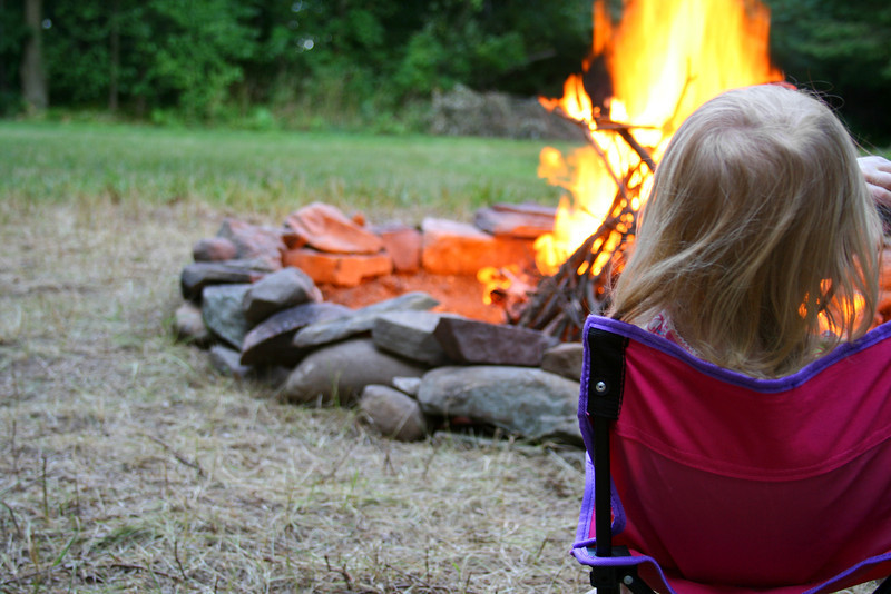 A child watches a bonfire in a stone fire pit.