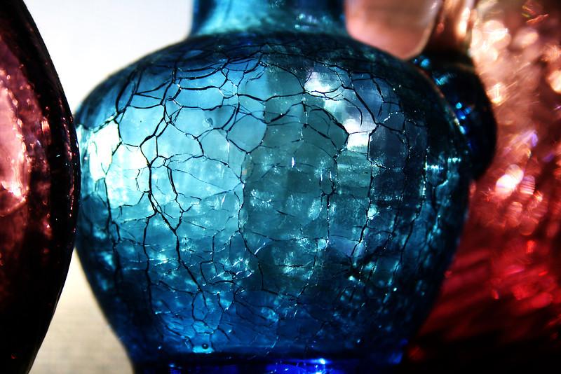 Sun glinting through a blue crackle glass vase.