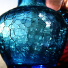 Sun glinting through a blue crackle glass vase.
