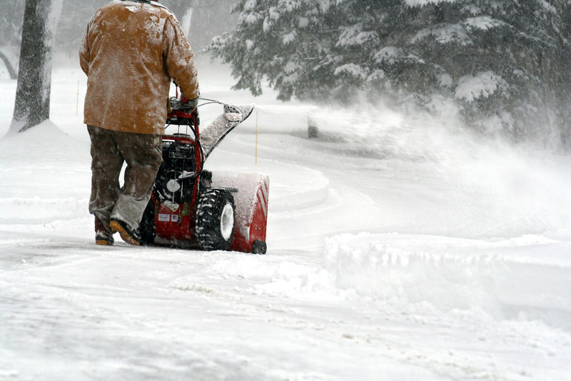 Snow-encased man drives a slow blower through Michigan drifts.