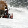 Snow-encased man drives a slow blower through Michigan drifts.