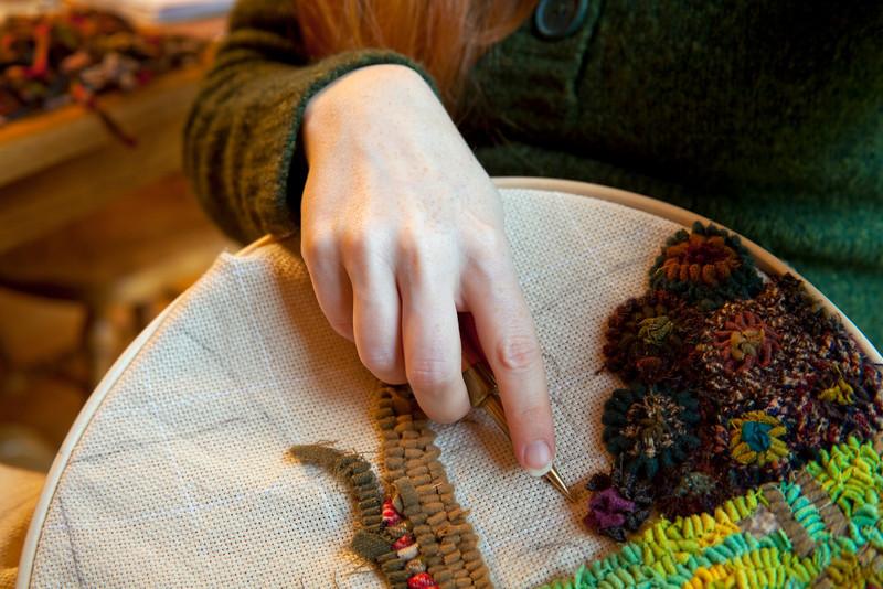 A woman hooks a traditional rug.