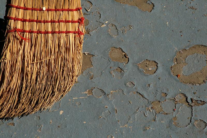 Rustic broom against peeling porch paint.