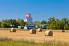 Large round hay bales and an elevator at Lena, Manitoba, Canada.