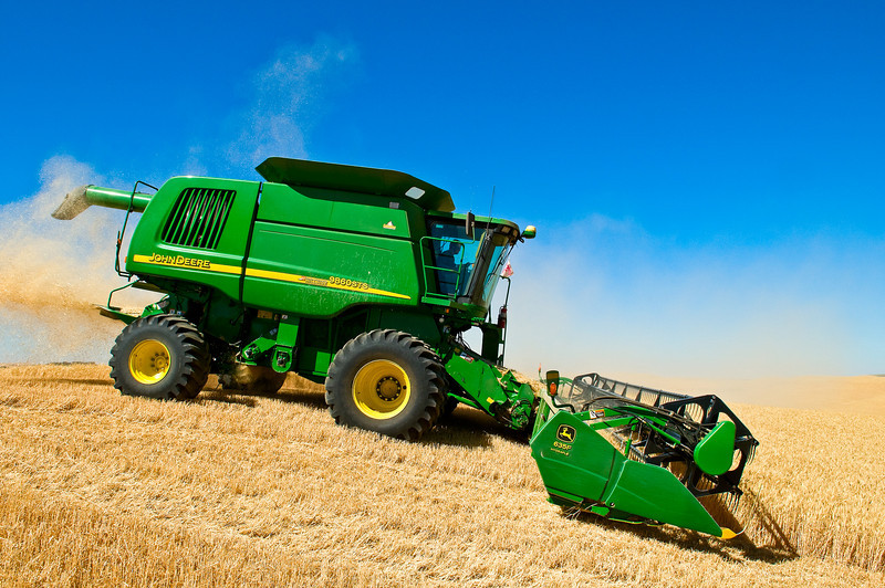 A combine starts down a steep hill to harvest wheat in the Palouse region of Washington
