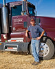 A truck driver stands next to his truck during harvest in the Palouse region of Washington