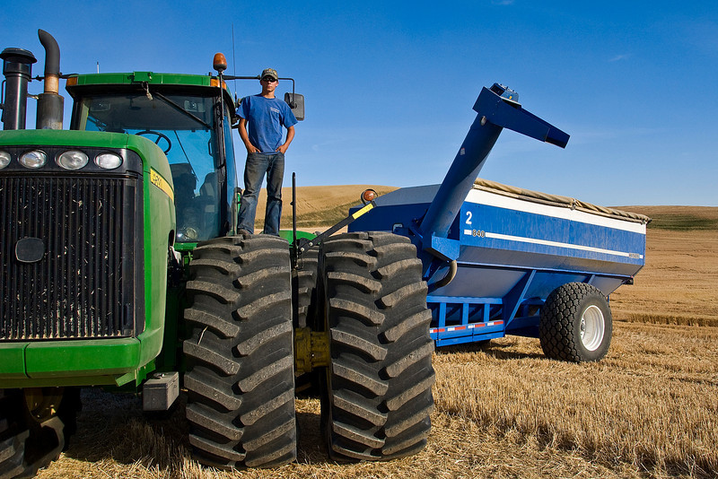 A tractor driver stands atop his tractor during harvest in the Palouse region of Washington