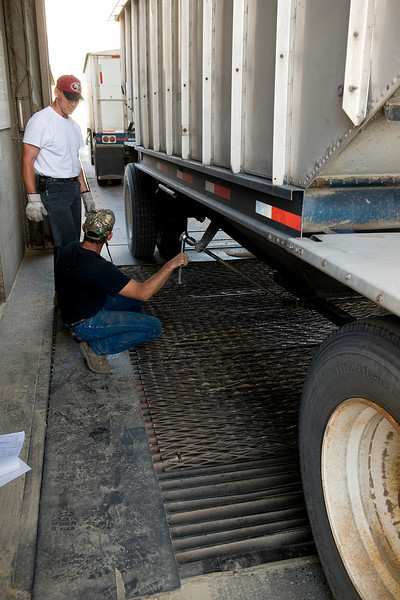 A truck driver operates the dump mechanism of his truck trailer at a grain storage facility during harvest in the Palouse region of Washington