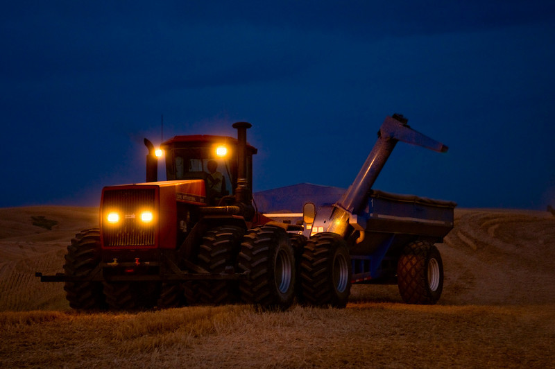 A tractor pulling a grain cart moves through a field in early evening twilight in the Palouse region of Washington