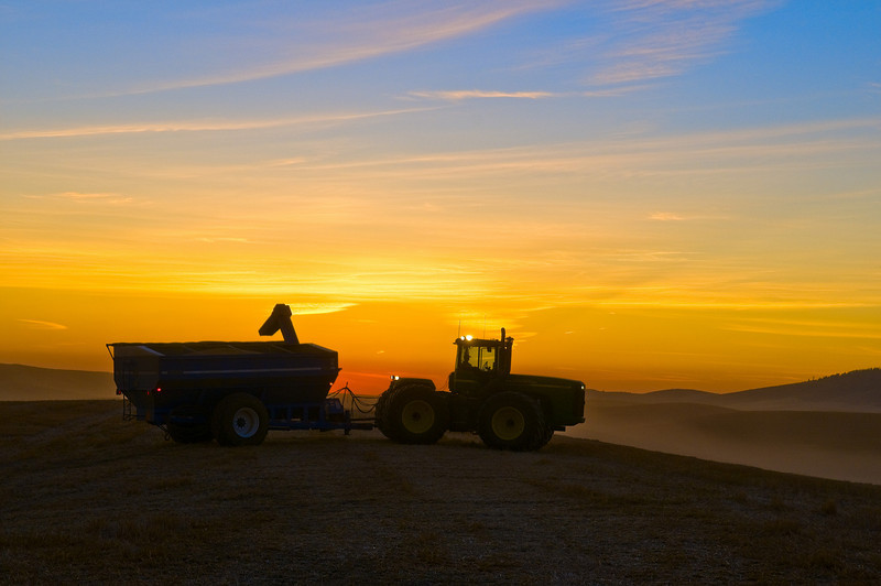 A tractor pulling a grain cart waits atop a hill at sunset in the Palouse region of Washington