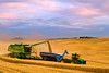 A combine harvests wheat in the Palouse region of Washington while unloading into a grain cart on the go