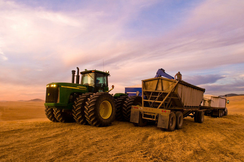 A tractor pulling a grain cart unloads into a truck at sunset in the Palouse region of Washington