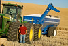 A tractor driver stands next to his tractor during harvest in the Palouse region of Washington