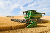 A pair of combines harvest wheat while one of them unloads on the go into a grain cart in the Palouse region of Washington