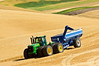 A tractor pulling a grain cart moves through a field during harvest in the Palouse region of Washington