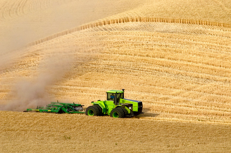 Disking wheat stubble during harvest to have a fire break in case of a field fire.