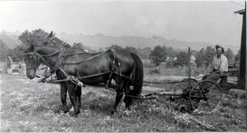 Team working an old mowing machine. (Photo ID: 28132)
