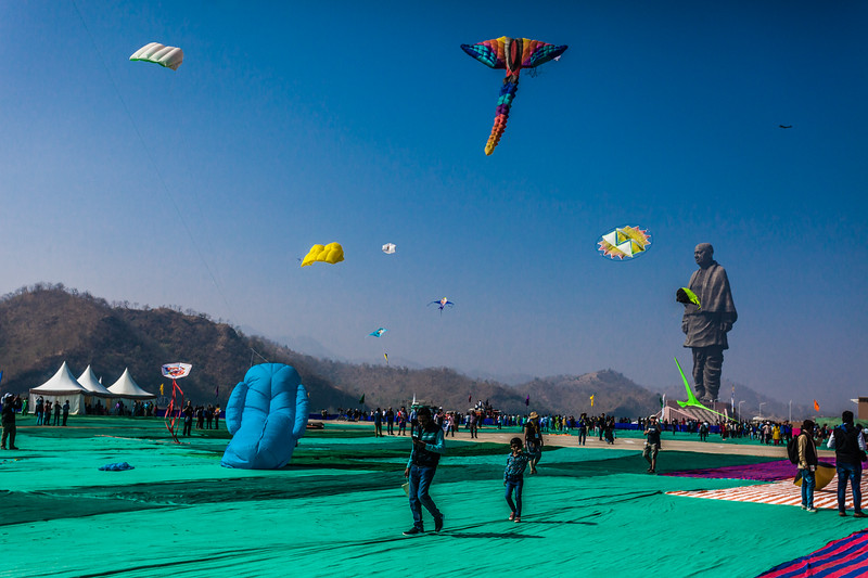 Kites flying high at the International Kite festival 2019 as the Statue of Unity looms large in the background at Kevadia, Gujarat, India