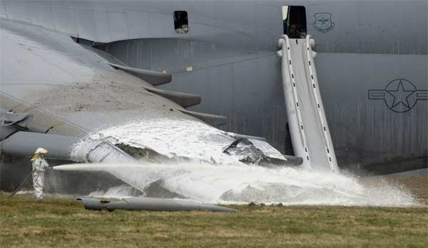 A firefighter hoses down the crash site of a C-5 Galaxy. The aircraft crashed at 6:30 a.m. EDT, on Monday, April 3, 2006, at Dover Air Force Base, Del., just south of the base flightline. All 17 people aboard survived the crash.
