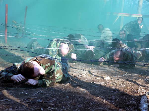 """Students in the Air Force Phoenix Raven Class 06-D at Fort Dix, N.J., move a """"patient"""" through an obstacle course during combat first aid training for the students."""