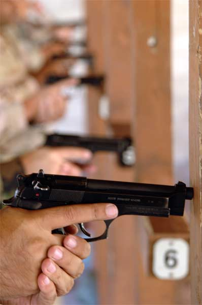 Servicemembers assigned to MacDill Air Force Base, Fla., take safety measures before firing the Beretta M-9 pistol during a combat arms training and maintenance class at MacDill Air Force Base, Fla., on Monday, March 27, 2006.