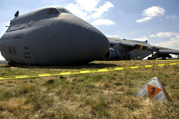 This C-5 Galaxy lies in a field on the south side of Dover Air Force Base, Del., after it crashed Monday, April 3, 2006. Specialists roped off the area with caution tape to preserve the scene until a safety investigation board completes its task.