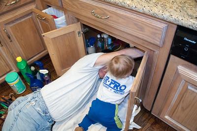 Grandson Phoenix is helping his PaPaw under the sink