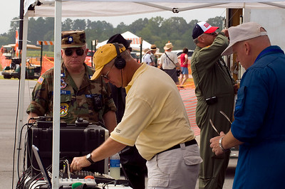 Show announcer Hugh Oldham (in yellow shirt and cap) gets ready for the show and adjusts the P/A system while a Civil Air Patrol Colonel looks on.